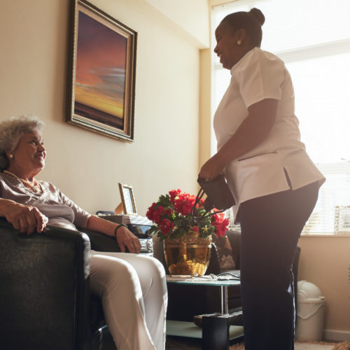 Senior woman sitting on a chair at home with female caregiver standing by. Female nurse visiting senior patient for checking blood pressure.